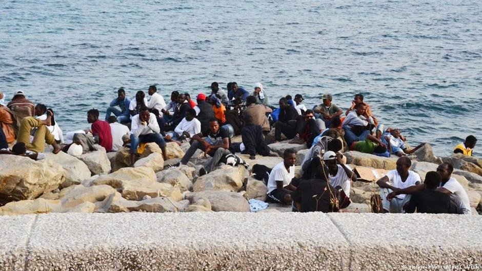 Migrants sit along the sea front at the border between France and Italy