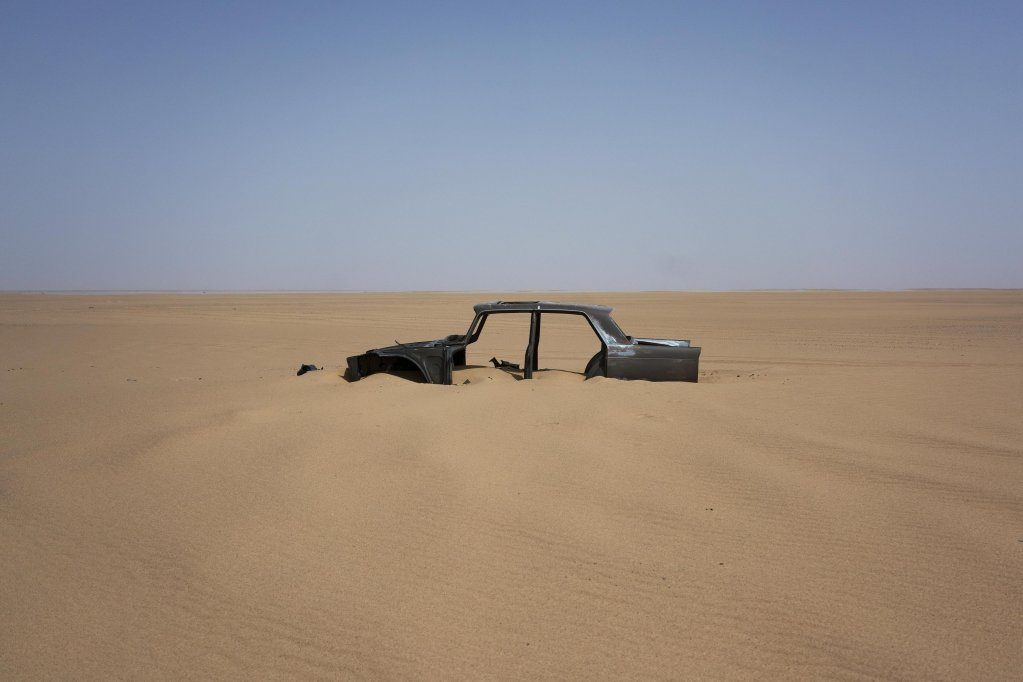 An abandoned car rests in Niger's Tenere desert region of the south central Sahara. Once a well-worn roadway for overlander tourists, the highway's 4,500 kilometers (2,800 miles) are a favored path for migrants heading north | Photo: ANSA/AP Photo/Jerome Delay