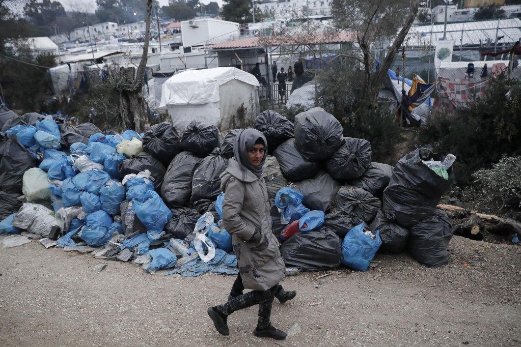 ANSA / مهاجرة مع طفلها يسيران إلى جوار أكوام القمامة في مخيم موريا بجزيرة ليسبوس اليونانية. المصدر: إي بي إيه / ديمتريس توسيديس.