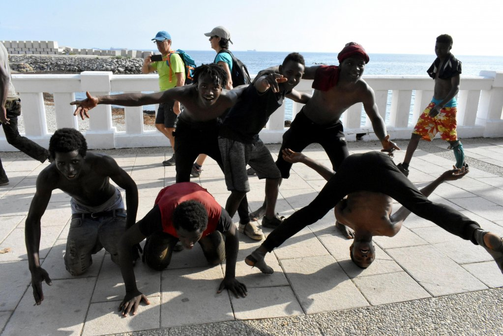 Sub-Saharan migrants celebrate as they wait outside of the Temporary Migrant Centre in Ceuta, the Spanish enclave in Morocco, on August 22, 2018, after some 200 people managed to climb over the border fence between Morocco and Spain. Credit: EPA/JOSE M. RINCON