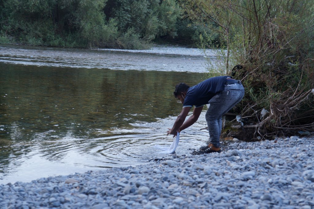 Abdelkhair, a migrant from Bangladesh, washes his clothes in the Roya River. Credit: InfoMigrants
