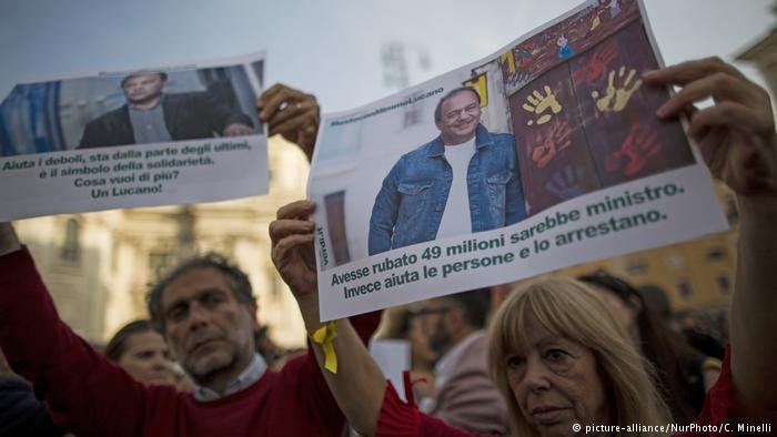 """Protesters have slammed Italian authorities for arresting Mayor Domenico Lucano, known by many as """"Mimmo."""" The placard on the right says: """"If he had stolen €49 million, he would be minister. Instead, he helps people and is arrested."""""""