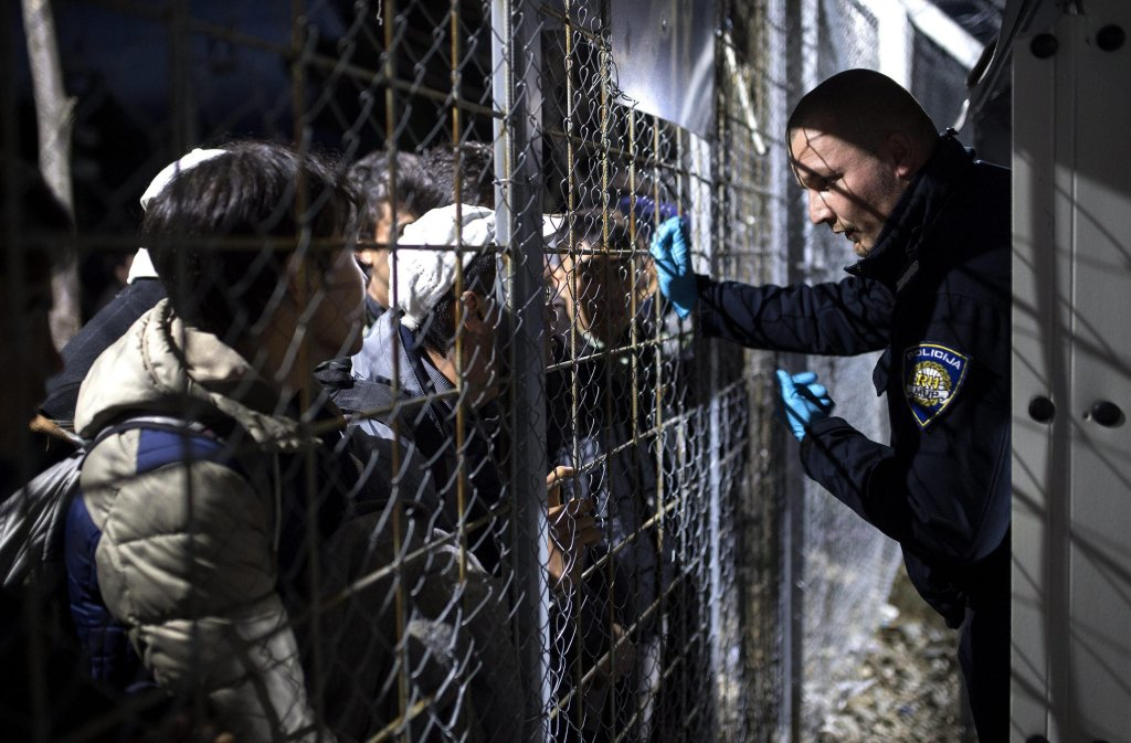 A Croatian police officer talks to refugees from Syria and Iraq waiting to cross the Greek-Macedonian border, near the Macedonian city of Gevgelia, 22 February 2016.  Photo: EPA/GEORGI LICOVSKI