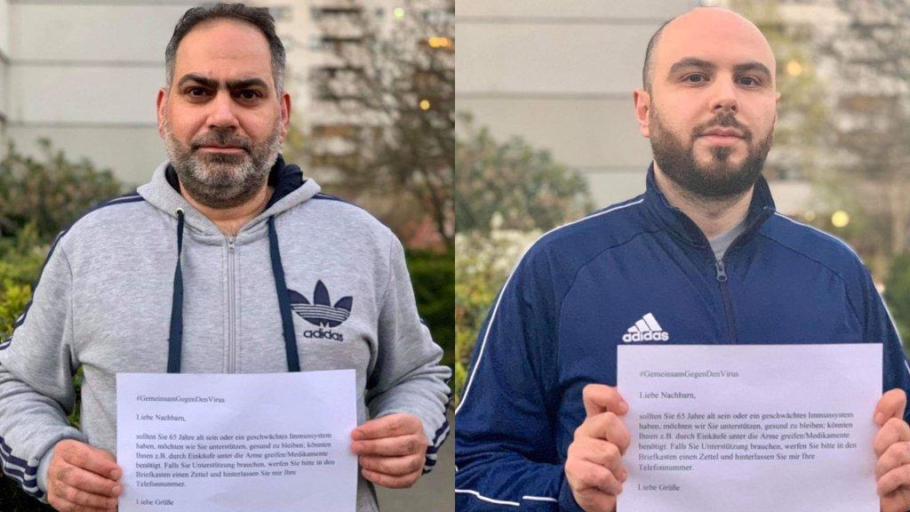 أحمد حورية إلى اليمين، وكمال الطويل إلى اليسار، يحملان الإعلانات التي علقوها على جدران مباني جيرانهم يعرضون فيها المساعدة لمن يحتاجها.