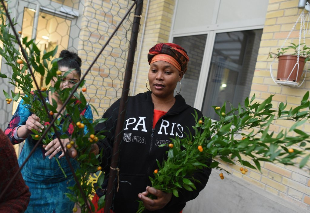 Ami, an asylum seeker from Ivory Coast, is dressing the floral arch. Photo: Mehdi Chebil