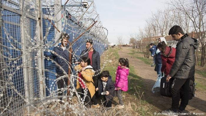 A picture of the Hungarian border and a family waiting outside it | Photo: Picture Alliance / Abaca / O. Marques