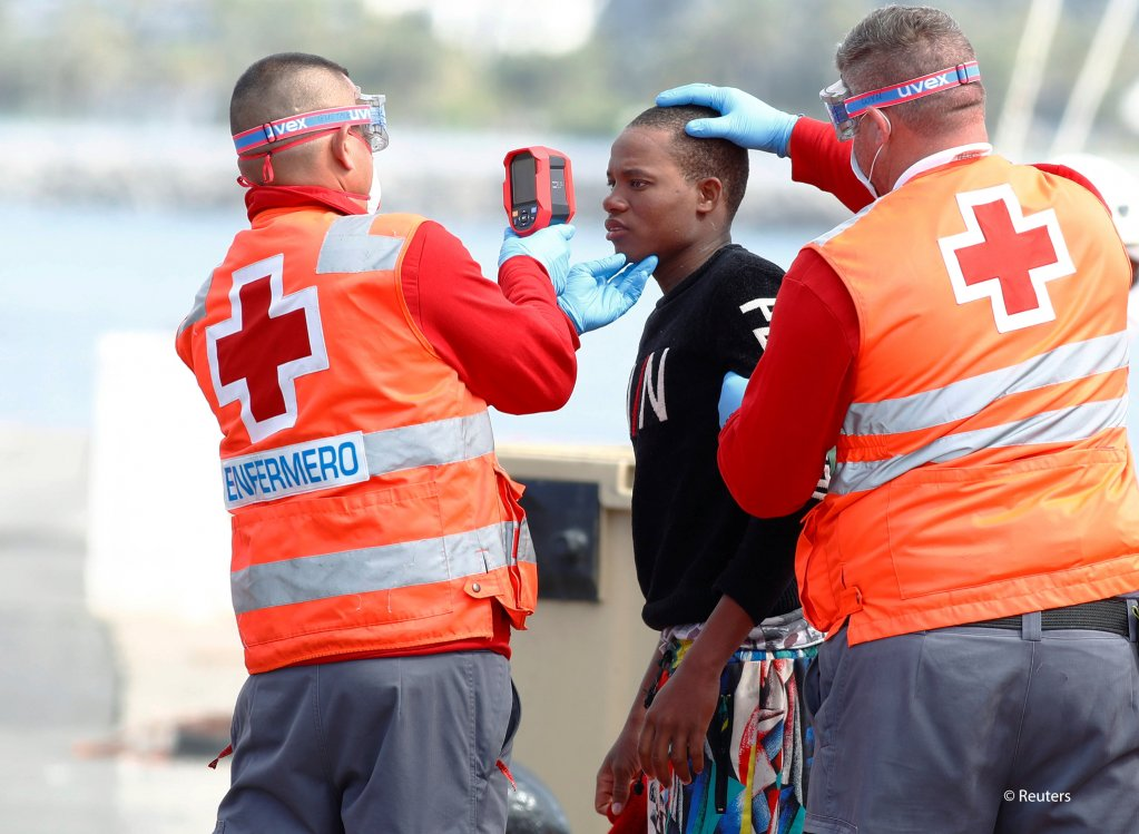 Red Cross members take the temperature of a migrant before disembarking from a Spanish coast guard vessel in the port of Arguineguin on the island of Gran Canaria Spain May 17 2020  Photo REUTERSBorja Suarez