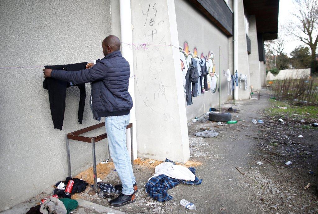 Un homme étend son linge à l'extérieur du gymnase occupé. Crédit : Reuters
