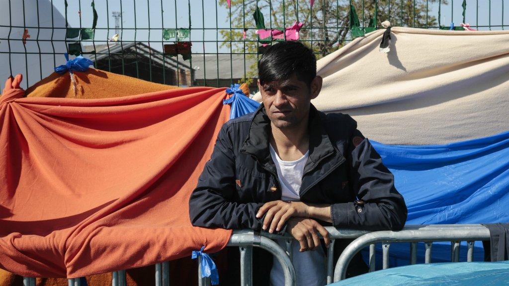 أ ف ب |مهاجر أفغاني ينتظر عند مدخل مخيم للاجئين بالقرب من بورت دو لاشابيل، شمال باريس