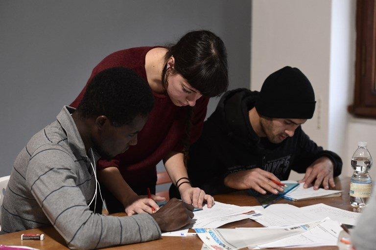©MIGUEL MEDINA/AFP |Une bénévole aide des migrants à étudier pendant un cours dans le cadre d'un programme d'aide à l'intégration des migrants, en Italie.