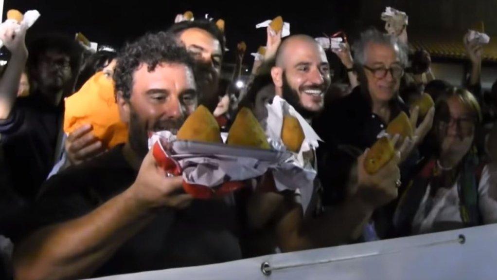 إيطاليون يحملون كرات الأرز المقلي للترحيب باللاجئين، كاتانيا، صقلية. 22 آب/ أغسطس 2018 | المصدر: لقطة من فيديو على مواقع التواصل