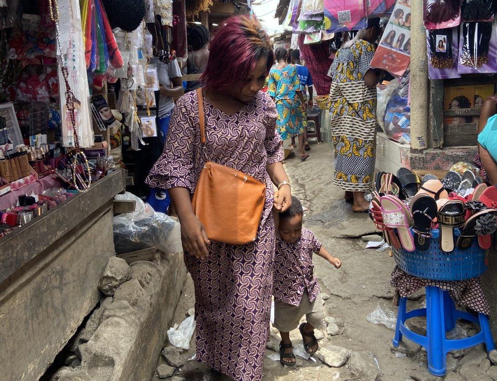 Yolande et son fils né au Maroc dans les allées du marché de Youpougon en banlieue d'Abidjan. Crédit : Anne-Diandra Louarn / InfoMigrants