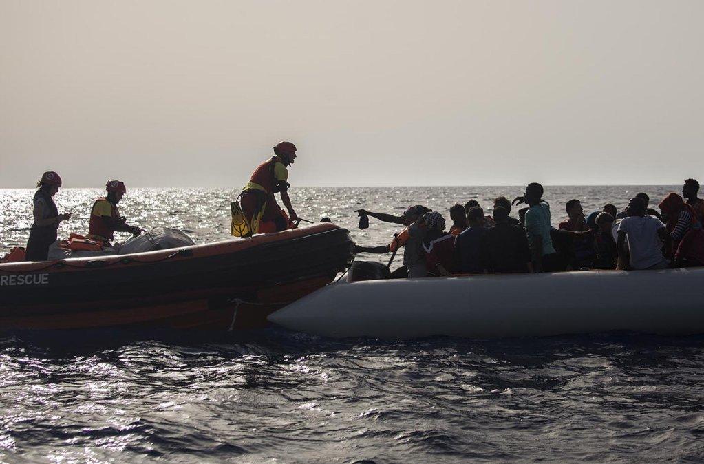"""ansa / مهاجرون على متن قارب مطاطي بالقرب من سواحل ليبيا يلوحون لعمال الإنقاذ على سفينة تابعة لمنظمة """"بروأكتيفا"""" غير الحكومية. المصدر: """"إي بي""""/ أنسا."""