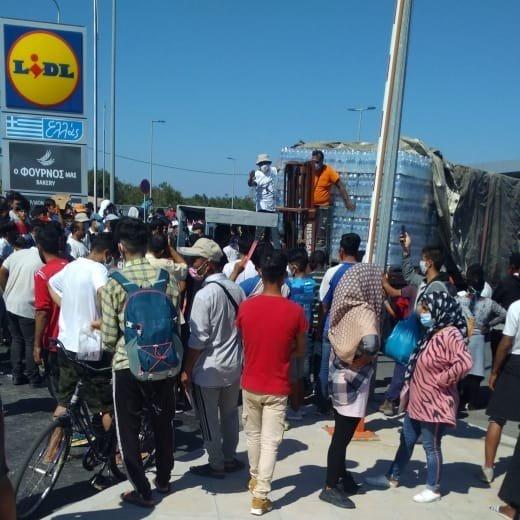 Sur le parking du supermarch Lidl de Lesbos de nombreuses personnes migrantes attendent une distribution deau Crdit  DR