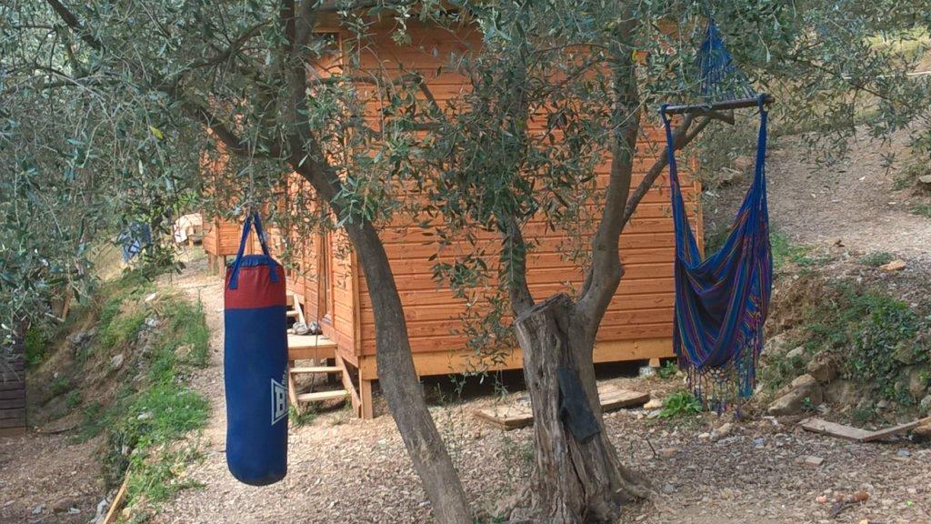 Un hamac et un punching ball sont installés à côté des cabanes dans lesquelles logent demandeurs d'asile et réfugié, chez Cédric Herrou, à Breil-sur-Roya. Crédit : Charlotte Oberti