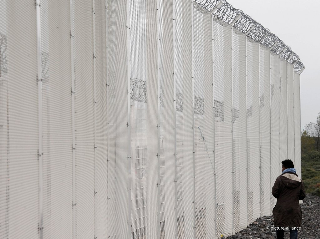 From file: A migrant stands near a fence installed to secure the Eurotunnel platform area near the migrant camp known as the new Jungle in Calais, northern France, October  21, 2015 | Photo: Picture-alliance/AP Photo