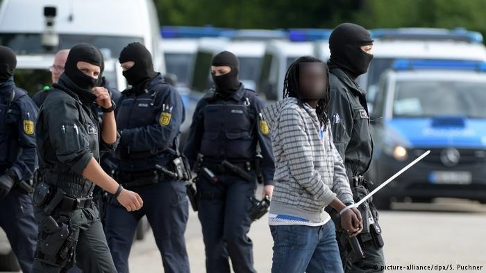 Police escort an asylum seeker away