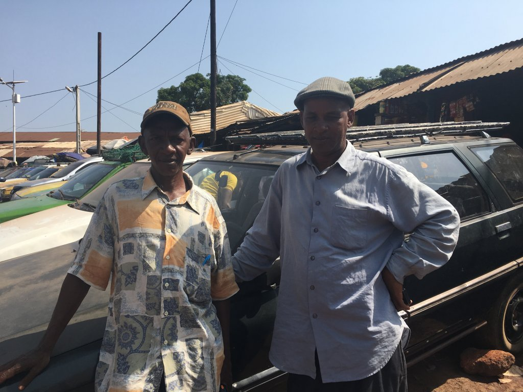 Montaga Sow and Mamadou Gando Diallo work for Mamou's transport workers' union. They encourage taxi drivers to be keep an eye out for departing youths. Photo: Julia Dumont