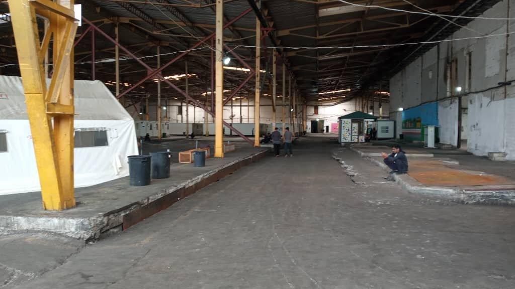 A Bira, les conteneurs, où dorment 6 à 10 personnes, sont abrités sous un hangar. Crédits : Arshid pour InfoMigrants.