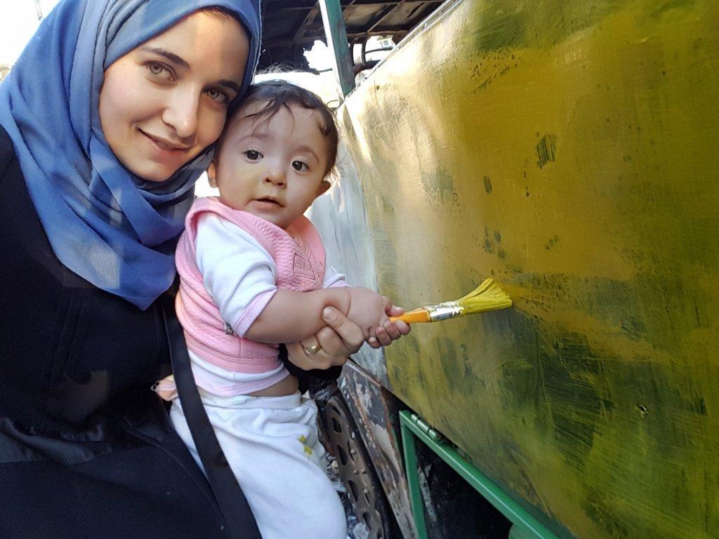 Waad et Sama repeignent un bus dtruit avec dautres enfants  Photo  avec la permission de la campagne Action for Sama