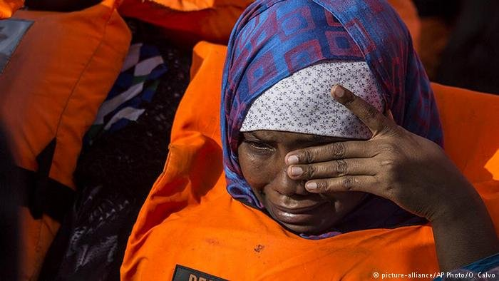 A woman wipes away tears as she and dozens of other migrants are rescued by the Open Arms, a ship operated by a Spanish NGO