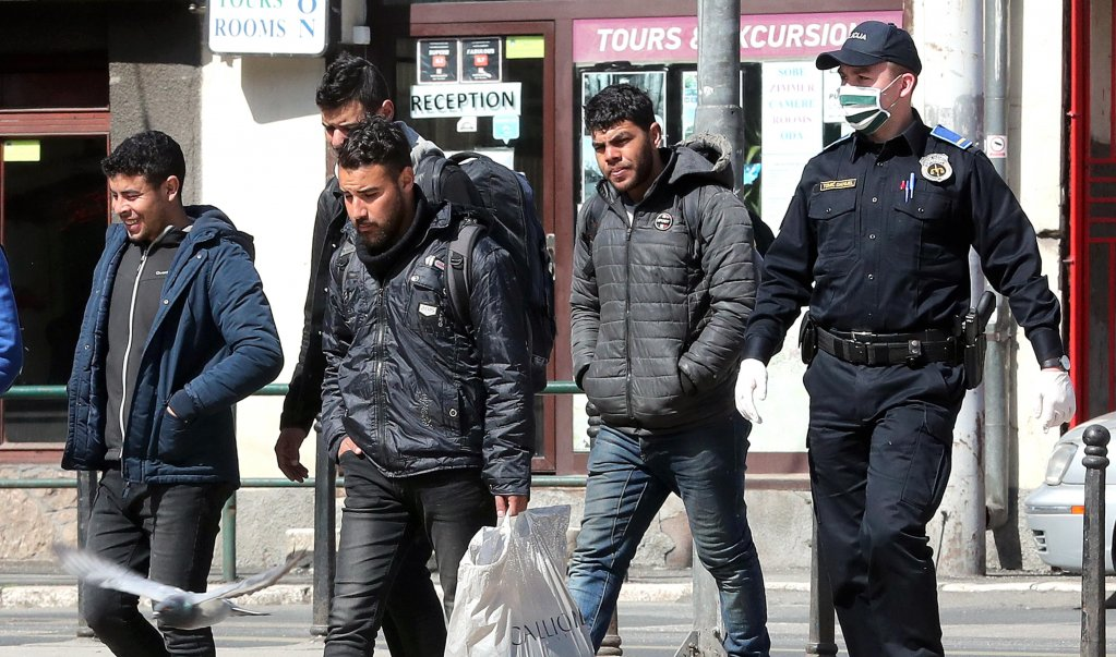 Bosnian police officers escorting migrants to a migration center in Sarajevo  Photo EPAEPAFEHIM DEMIR