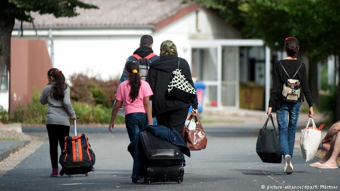 A refugee family pulling suitcases/ Germany