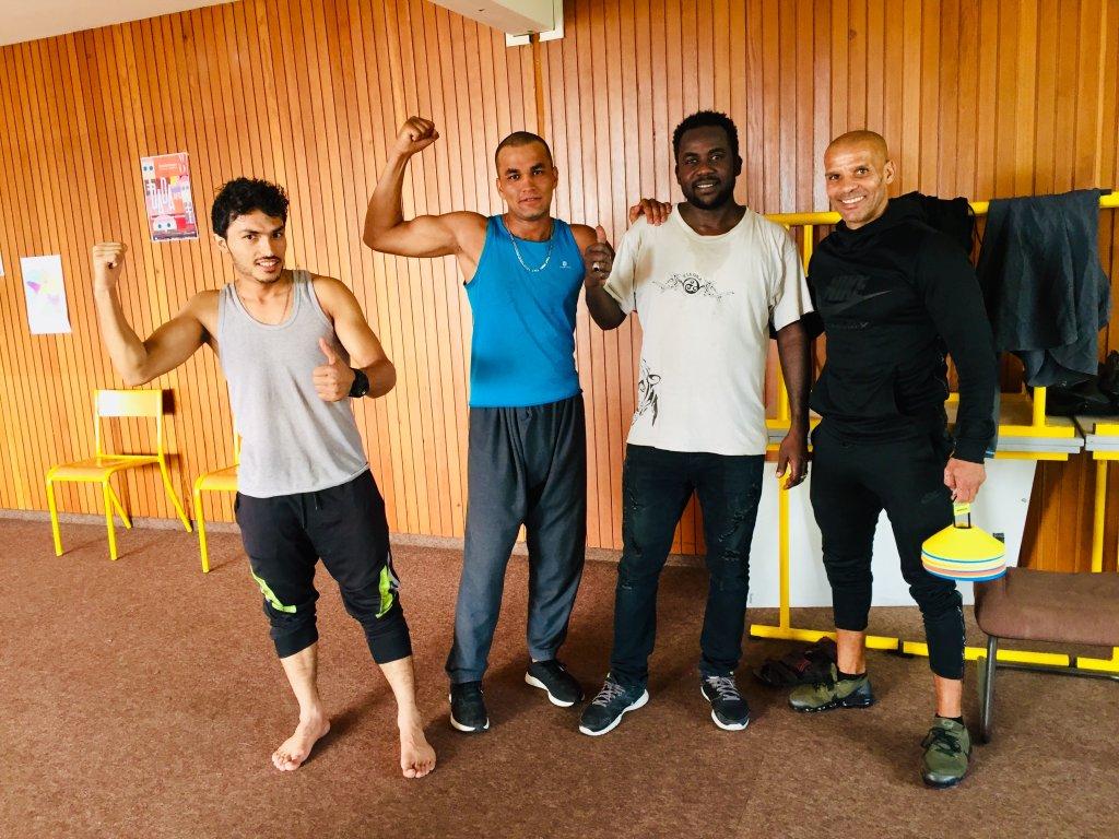 Le réfugié afghan Nasir Safi (gauche), son coach sportif Mohamed Barhoumi (droite) et plusieurs résidents du centre d'hébergement de la Rochefoucauld à Paris. Crédits photo : Anne-Diandra Louarn/InfoMigrants