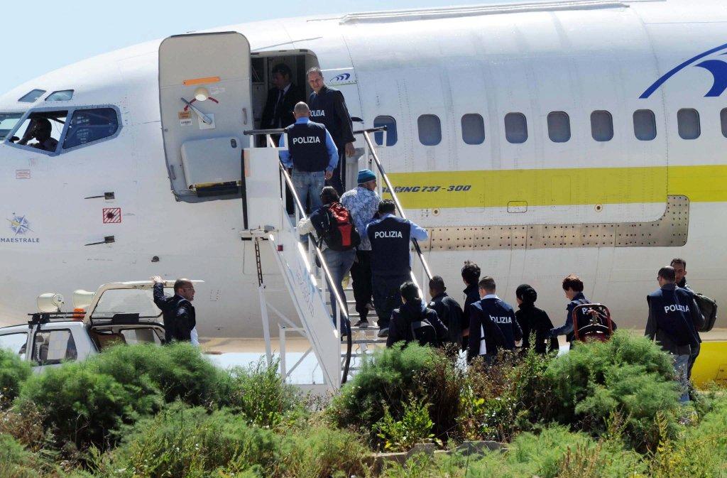 Italian police officers escorting migrants to a plane | Photo: EPA/CARLO FERRARO