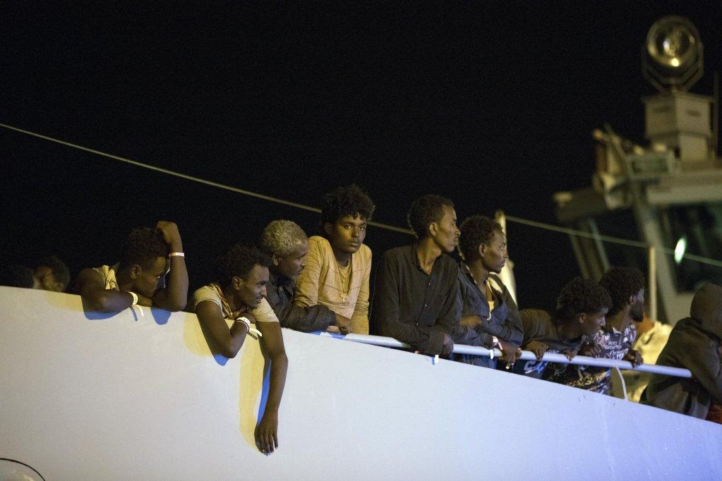 """ansa / مهاجرون يهبطون من سفينة """"بروتيكتور"""" التابعة لفرونتكس في منتصف الليل في ميناء بوزالو بصقلية، ومن بينهم امرأة حامل وأم تحمل رضيعها، وطفل عمره 3 سنوات. المصدر: أنسا/ فرانشيسكو روتا"""
