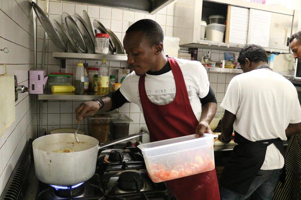 A young migrant prepares a dish in the Gustamundo kitchen (ANSA)