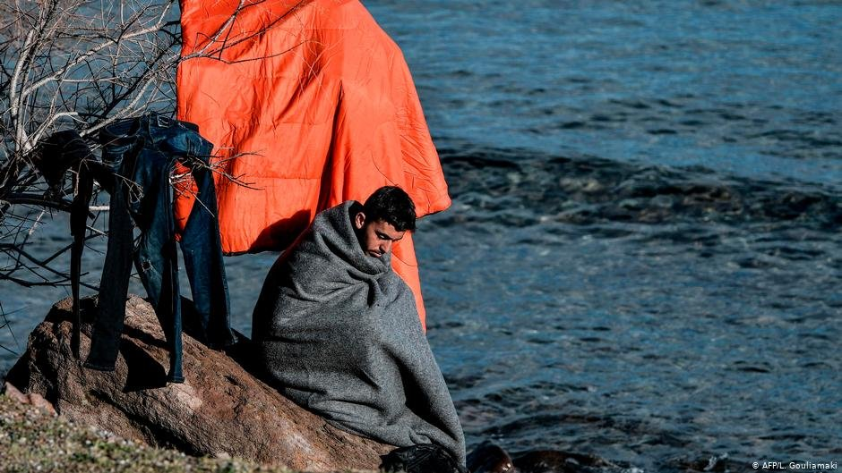 A migrants wraps himself in a blanket while drying his clothes  Photo AFPL Gouliamaki