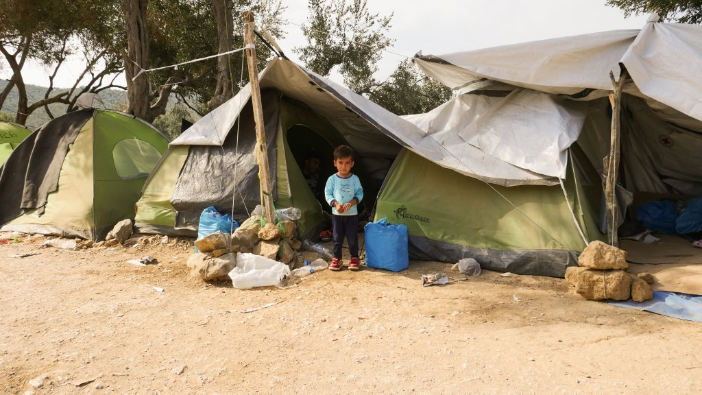 Afghan child standing in front of his familys tent in the Olive Grove on Lesbos  Photo Aasim Saleem