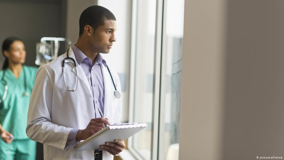 A doctor looks out of a window at a hospital  Photo Picture-alliance