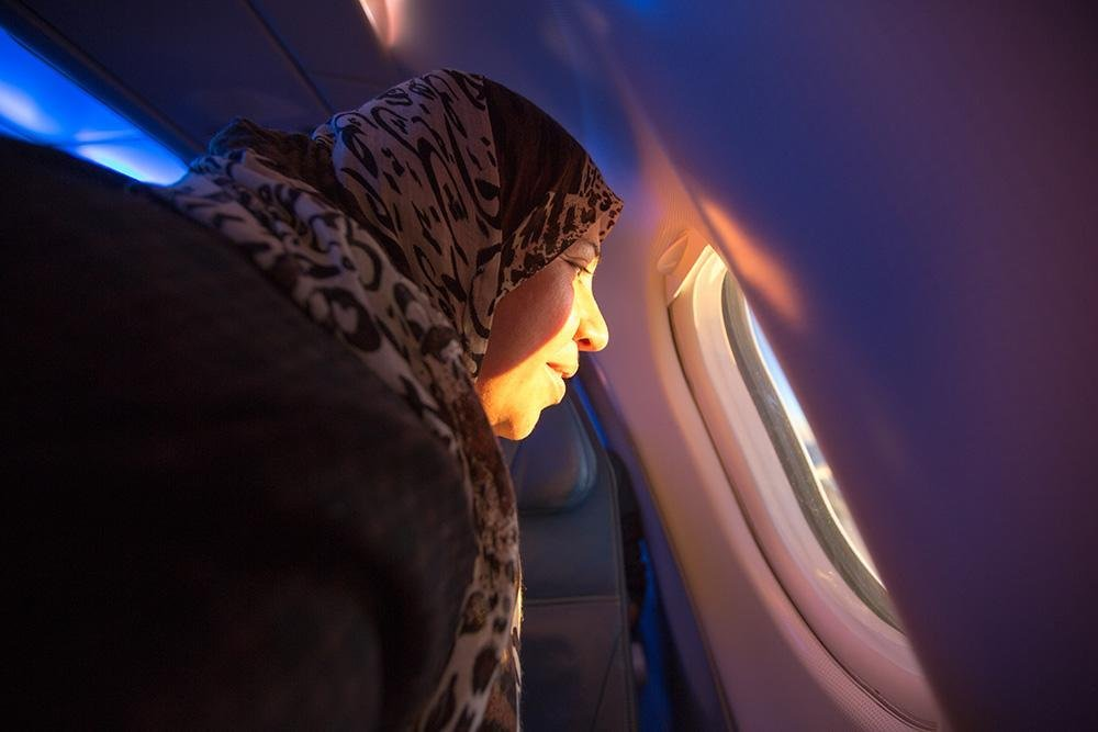 A woman looks out a an airplane window during a resettlement flight Image credit: IOM/M.Mohammed)