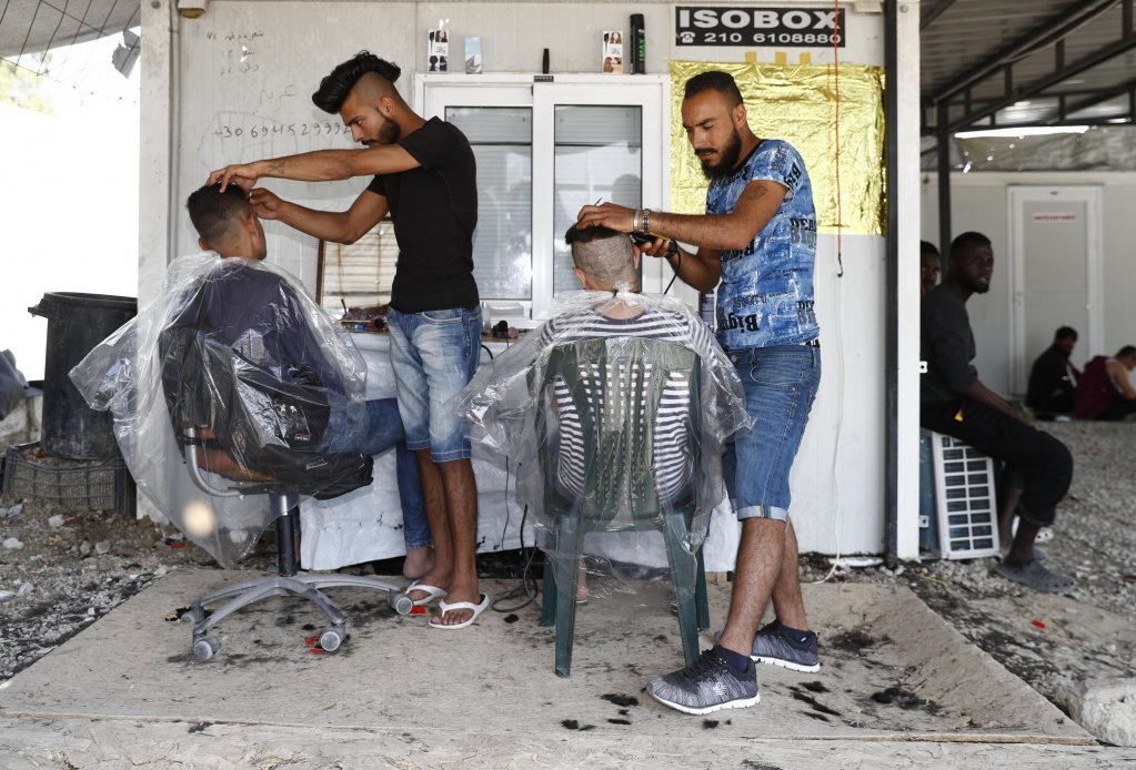 Refugees from Iraq cut the hair of other refugees in the Moria refugee camp on the island of Lesbos, Greece (archive/EPA)