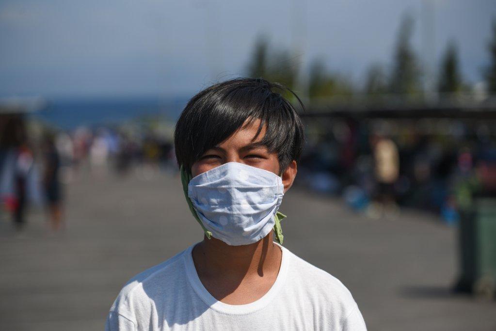 أبو الفضل (13 عاما)  يرتدي كمامة وزعتها جمعية عائلة سعيدة بعد حريق مخيم موريا. المصدر: مهدي شبيل/مهاجر نيوز