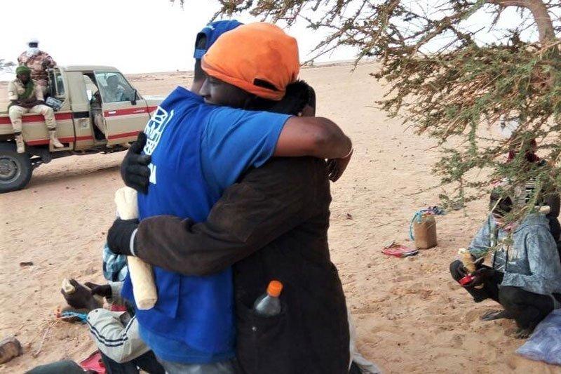 Un sauveteur de l'OIM serre dans ses bras un migrant secouru dans le désert de Ténéré. Crédit : OIM