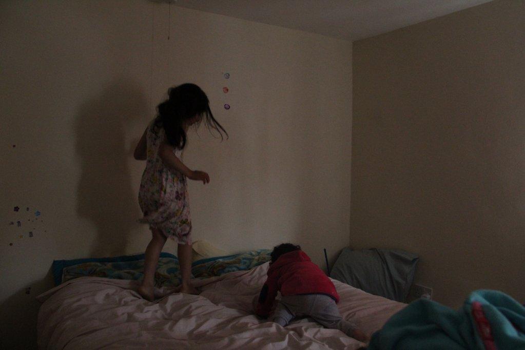 Hema et Mina jouent sur leur lit à Stock-on-Trent. Crédit : Brenna Daldorph