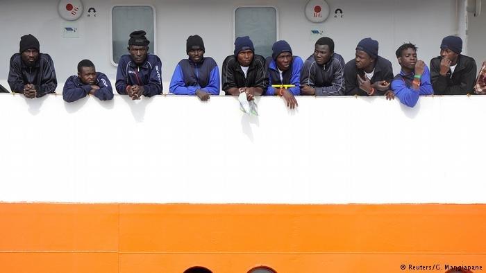 Migrants wait to disembark in Sicily
