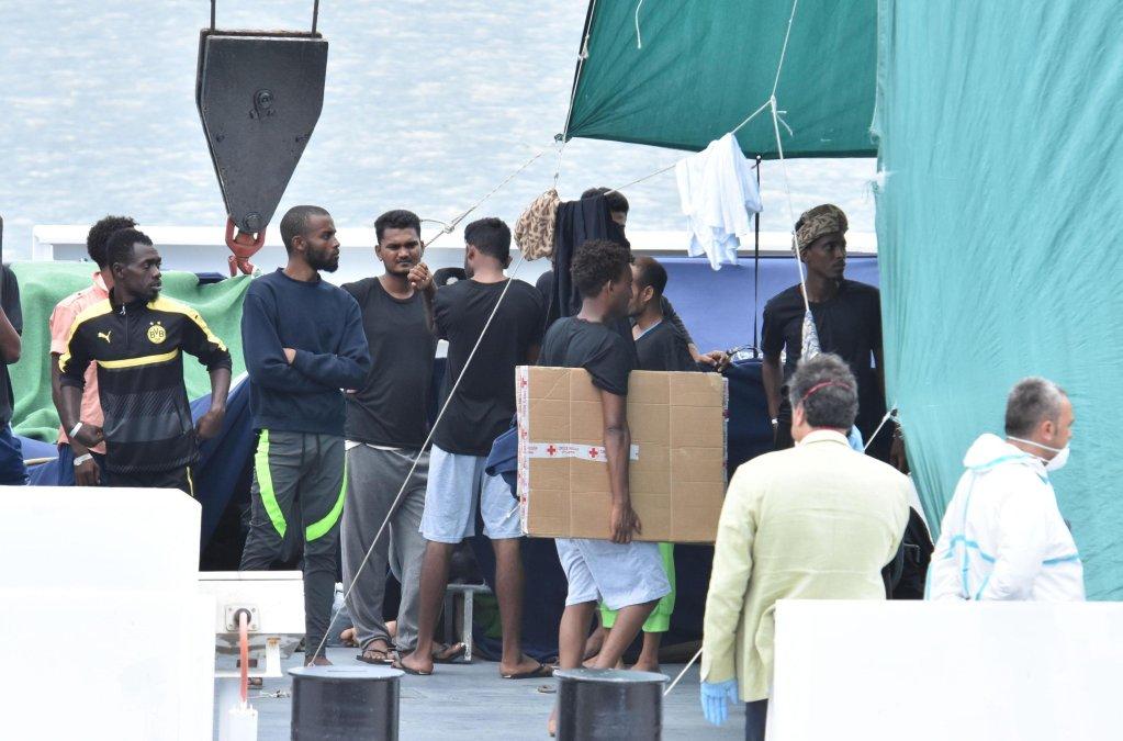 """مهاجرون ينتظرون الهبوط من سفينة حرس السواحل الإيطالي """"ديتشيوتي"""" في ميناء كاتانيا الإيطالي في آب/أغسطس الماضي. المصدر: أنسا/ اوريتا سكاردينو"""