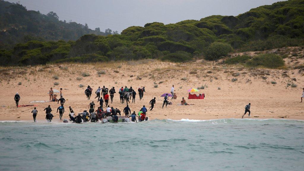 مهاجرون ينزلون من زورق صغير على شاطئ ديل كانويلو بعد عبورهم مضيق جبل طارق-رويترز