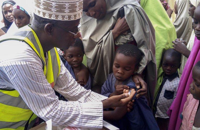 Nigerian doctor Rilwanu Mohammed (L), executive secretary of the federal capital's Primary Health Care Development Board, vaccinates a resident for meningitis in Dakwa village, Bwari, Nigeria, 4 April 2017. EPA/Deji Yake