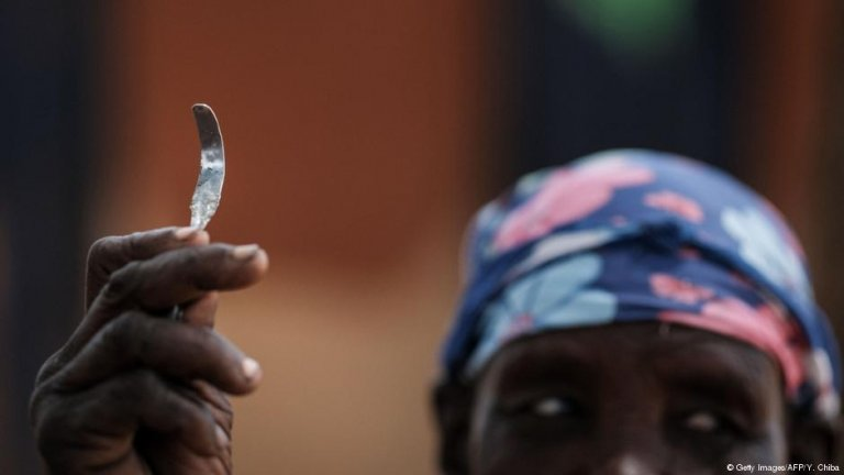 A woman with a rough blade used for FGM in Uganda | Photo: Getty Images/AFP/Y.Chiba