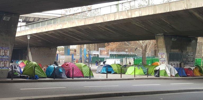 Des dizaines de tentes sont rassemblées sous un pont Porte de la Chapelle. Crédit : InfoMigrants
