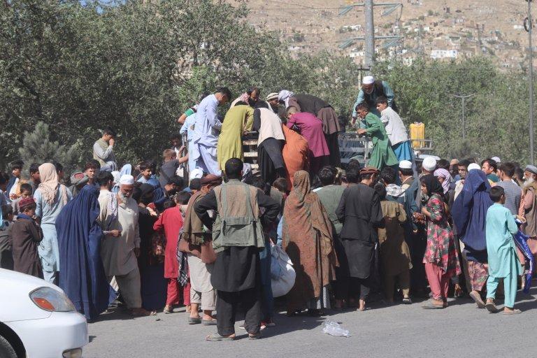 نازحون من مقاطعتي قندوز وتخار، بسبب القتال بين طالبان والقوات الأفغانية، يتجمعون للحصول على الطعام، حيث يعيشون في معسكر في كابول. المصدر: إي بي إيه/ جواد كارجار.
