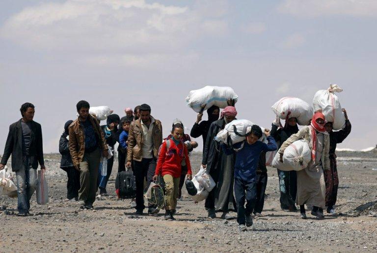 نازحون سوريون من الرقة يحملون أغراضهم أثناء خروجهم من مخيم عين عيسى في سوريا/ َANSA