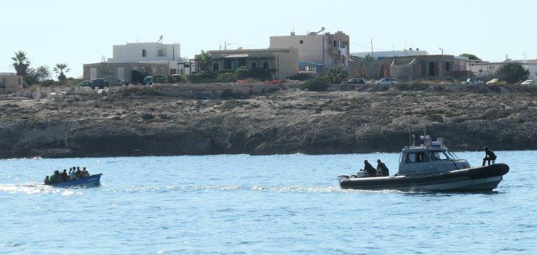 ANSA / إحدى وحدات حرس السواحل الإيطالية ترافق قاربا مليئاً بالمهاجرين إلى لامبيدوزا. المصدر: أنسا / إيليو ديسيديريو.