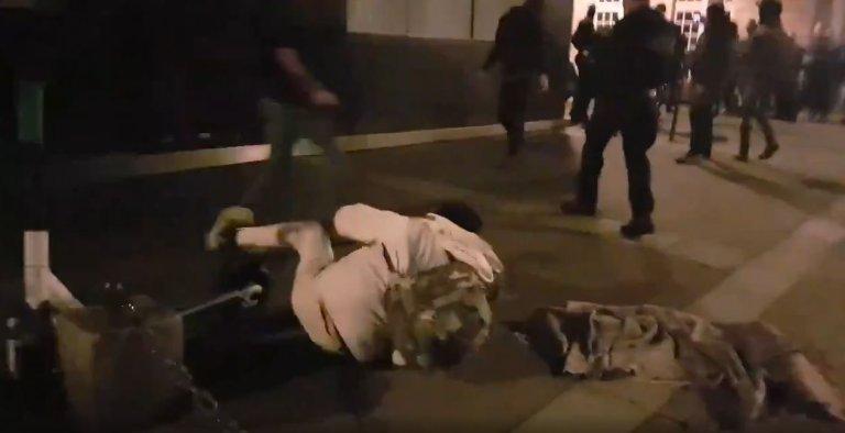 Un migrant à terre à Paris avoir été stoppé dans sa course par le croche-pied d'un policier, lundi 23 novembre. Crédit : capture d'écran Twitter