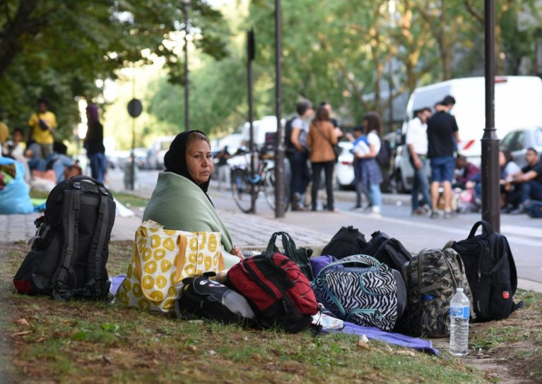 A migrant waits in a park at Porte d'Aubervilliers in the north of Paris for the Utopia 56 association to find emergency accommodation for her family. Credit: Mehdi Chebil